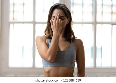 Young sporty woman practicing yoga, doing Alternate Nostril Breathing exercise, nadi shodhana pranayama pose, working out, wearing sportswear, grey top, indoor close up, white yoga studio