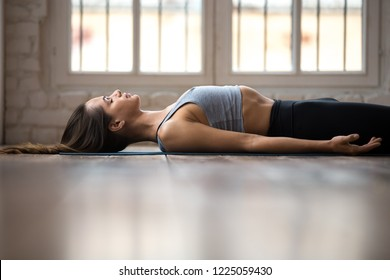 Young sporty woman practicing yoga, doing Dead Body, Savasana exercise, Corpse pose, working out, wearing sportswear, black pants and top, indoor close up, white yoga studio. Well-being concept