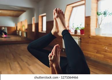 Young sporty woman practicing yoga, doing Alternate Nostril Breathing exercise, nadi shodhana pranayama pose, working out, wearing sportswear, grey top, indoor close up, white yoga studio.
