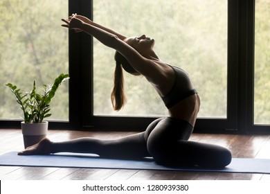 Young sporty woman practicing yoga, doing Single Pigeon exercise, Eka Pada Raja Kapotasana, One Legged pose, working out, wearing sportswear, grey pants and top, indoor full length, yoga studio