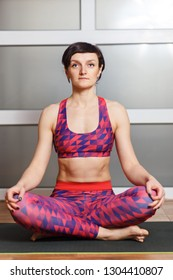 Young sporty woman practicing yoga, doing Sukhasana exercise, Easy Seat pose, working out, wearing sportswear, red pants and top, indoor full length, fitnes club