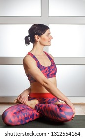Young sporty woman practicing yoga, doing Padmasana exercise, Easy Seat pose, working out, wearing sportswear, red pants and top, indoor full length, fitnes club