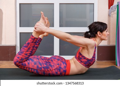Young sporty woman practicing yoga, doing Dhanurasana stretching position in a fitnes club.