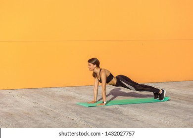 Young sporty woman practicing yoga, doing push ups or press ups exercise, phalankasana, plank pose, working out, wearing sportswear, black pants and top, Side view, outdoor, orange wall background