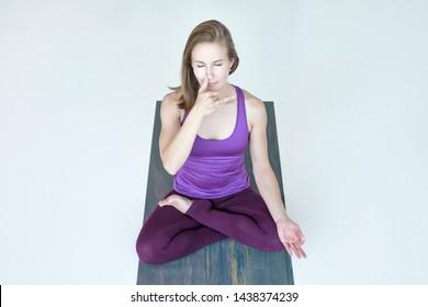 Young sporty woman practicing yoga, doing lotus exercise, breathing nadi shodhana pranayama. Top view.