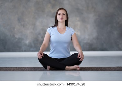 Young sporty woman practicing yoga, doing Sukhasana exercise, Easy Seat pose, working out. Indoor full length on gray background