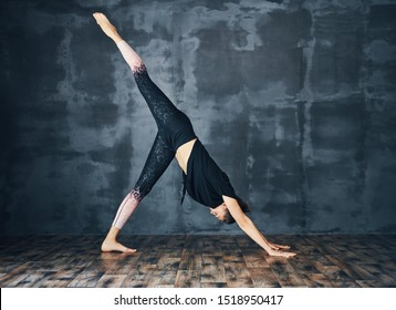 Young sporty woman practicing yoga, doing one legged downward facing dog pose (Eka Pada Adho Mukha Svanasana) on dark background
