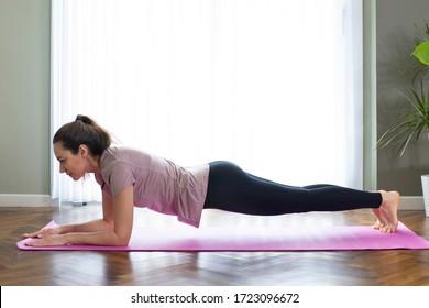 Junge Sportlerin, die Yoga praktiziert, Liegestütze macht. Plane Pose und Training. Sie trainiert zu Hause in einem Wohnzimmer.