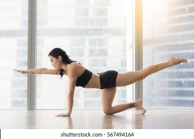 Young sporty woman practicing yoga, stretching in Donkey Kick, exercise, Bird dog pose, working out, wearing sportswear, black tank top, shorts, indoor full length, near floor window with city view