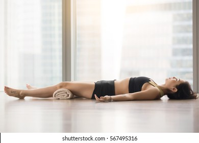 Young sporty woman practicing yoga, lying in Corpse, Dead Body exercise, Savasana pose, working out, wearing sportswear, black tank top, shorts, indoor full length, near floor window with city view