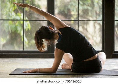 Young sporty woman practicing yoga at home, doing Side bending exercise, Sukhasana pose, model working out, wearing sportswear, black shorts and top, indoor full length, window background, rear view