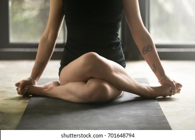 Young sporty woman practicing yoga at home, sitting in Gomukasana exercise, Cow Face pose, working out, wearing sportswear black shorts, top, indoor close up image, studio background. Wellness concept