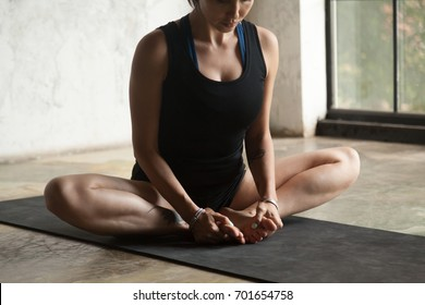 Young sporty woman practicing yoga at home, sitting in Butterfly exercise, baddha konasana pose, working out, wearing sportswear, black shorts and top, indoor close up image, studio background