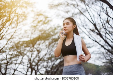 young sporty woman resting and wiping her sweat with a towel after workout sport exercises outdoors at the park