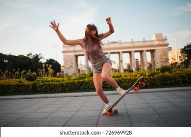 Young sporty woman riding on the longboard in the park