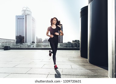 Young sporty woman running against urban background