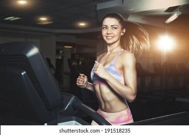 Young sporty woman running on machine in the gym and listening music in headphones