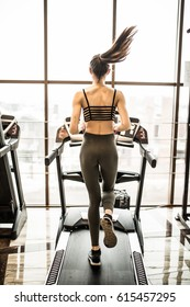 Young sporty woman running on treadmill in gym