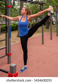 Young sporty woman stretches the leg