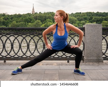 Young sporty woman stretches the legs