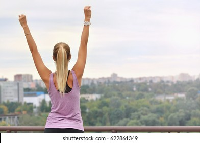 Young sporty woman stretching arms, preparing for working out, outdoor training, warming up after or before fitness on fresh air. Feeling freedom and relaxed