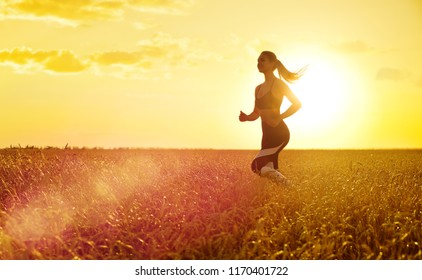 Young sporty woman at sunset in wheat field