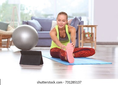 Young sporty woman with tablet practicing yoga at home