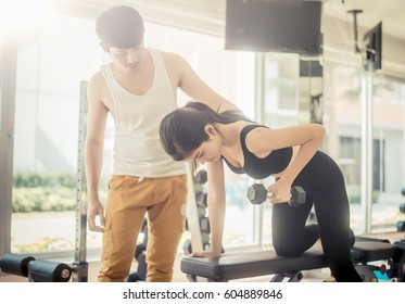 young sporty woman with trainer exercise weights lifting in fitness gym with vintage color