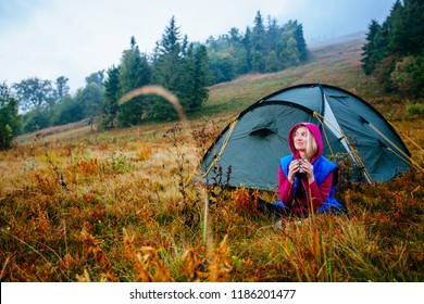 Young sporty woman travler drinking coffee campsite in the autumn cold morning. Meet morning, new day weekend concept