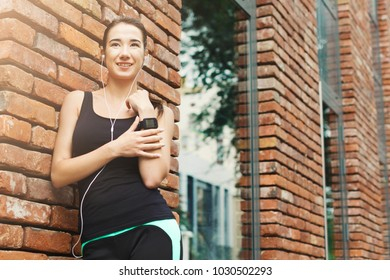 Young sporty woman using smart watch, listening to music, standing at brick wall background, copy space. Modern technology and fitness concept