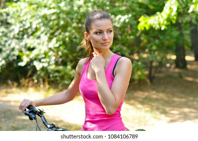 Young sporty woman walking in Park with bike and looks into the distance