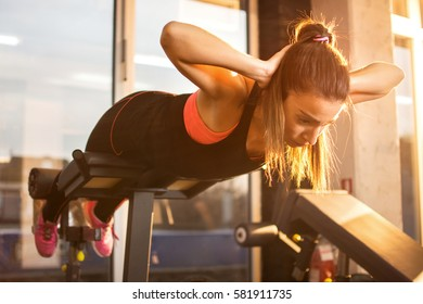 Young sporty woman workout on exercises machine in gym.