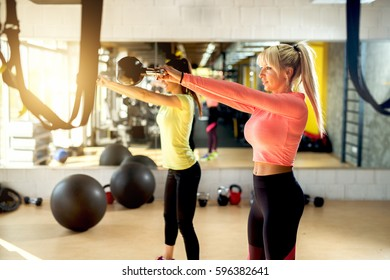 Young sporty women in comfy sportswear   swing kettlebell up with two arms training at gym