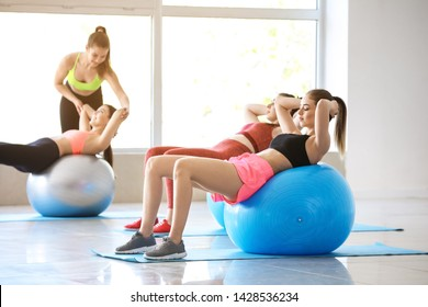 Young sporty women doing exercises with fitballs in gym
