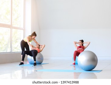 Young sporty women with fitballs doing exercises under supervision of trainer in gym