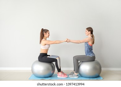 Young sporty women with fitballs doing exercises near light wall