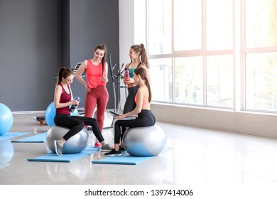 Young sporty women with fitballs drinking bottle in gym