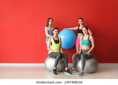 Young sporty women with fitballs near color wall