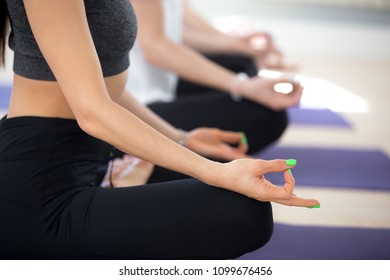 Young sporty women practicing yoga lesson, doing Easy Seat exercise, Sukhasana pose, working out, indoor session close up of hand mudra, girl with spring green manicure, studio. Wellbeing lifestyle