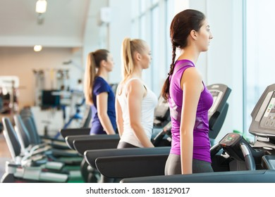 young sporty women run on machine in the gym centre