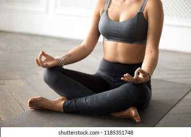 Young sporty yogi woman practicing yoga, doing Easy Seat exercise, Sukhasana pose, working out, wearing sportswear, grey pants, top, indoor close up, at yoga studio. Hobby wellbeing activity concept