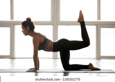 Young sporty yogi woman practicing yoga, doing Donkey, Kick exercise, Bird dog pose, working out, wearing sportswear, grey pants, top, indoor full length, at yoga studio