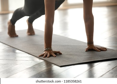 Young sporty yogi woman practicing yoga, doing Push ups or press ups exercise, phalankasana, Plank pose, working out, wearing sportswear, indoor close up, at yoga studio