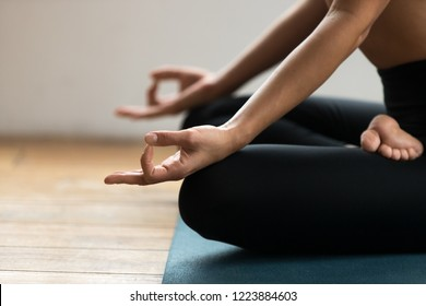 Young sporty yogi woman practicing yoga, doing Ardha Padmasana exercise, Half Lotus pose with mudra gesture, working out, wearing sportswear pants, indoor close up, yoga studio. Well-being concept