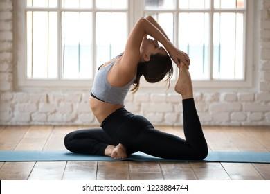 Young sporty yogi woman practicing yoga, doing One Legged King Pigeon exercise, Eka Pada Rajakapotasana pose, working out, wearing sportswear, pants and top, indoor full length, white yoga studio