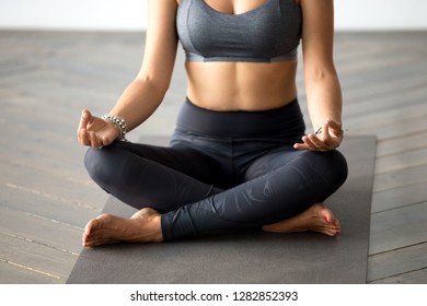 Young sporty yogi woman practicing yoga, doing Easy Seat exercise, Sukhasana pose, working out wearing sportswear grey pants, top, indoor body and legs close up at yoga studio. Hobby wellbeing concept