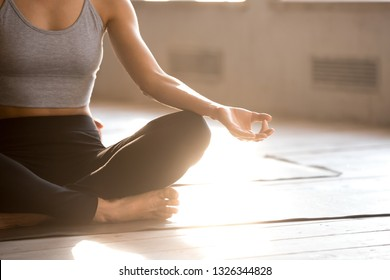 Young sporty yogi woman practicing yoga, doing Easy Seat exercise, Sukhasana pose, working out, wearing sportswear, black pants, top, indoor close up, yoga studio. Well being, wellness concept