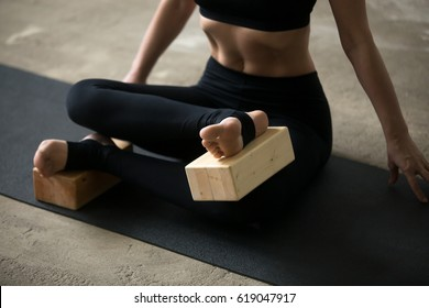 Young sporty yogi woman practicing yoga concept, sitting in Agni stambhasana exercise, Fire Log, Ankle to Knee pose, using wooden block, working out, black mat background, legs close up