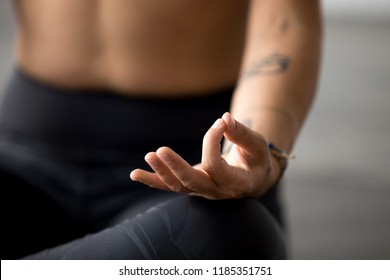 Young sporty yogi yoga woman meditating doing Easy Seat exercise, Sukhasana pose with mudra, working out, indoor hand close up, at yoga studio, focus on fingers. Hobby wellbeing activity concept