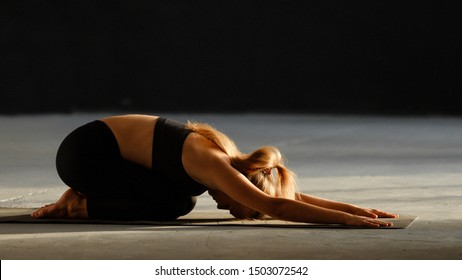 Young spotty girl and sporty man practice yoga, doing kid pose - Balasana. Training in a club, yoga studio. Wellbeing, fitness concept